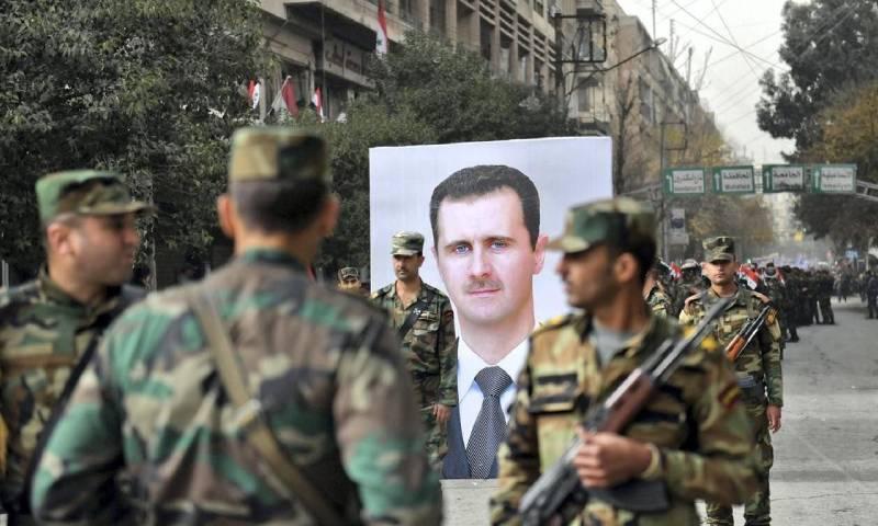 جنود سوريون يمرون أمام صورة رئيس النظام السوري بشار الأسد خلال ذكرى مرور عام على دخول قوات النظام مدينة حلب- 21 من كانون الأول 2017 (AFP)