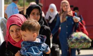 نساء وطفل لاجئ من سوريا يسيران باتجاه مخيم للاجئين في كوكينوتريميثيا، خارج العاصمة نيقوسيا، في جزيرة قبرص شرق البحر المتوسط - 10 أيلول 2017 (AP)