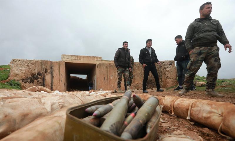 جنود سوريون يقفون قرب أسلحة وجدت في درعا - شباط 2018 (AFP)