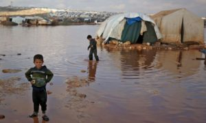 أطفال يلعبون بين الخيام التي غمرتها المياه في مخيم للنازحين السوريين بالقرب من بلدة كفرلوسين في إدلب. 26 من آذار 2021 (AFP)