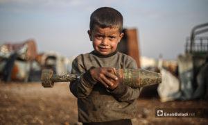 يحمل الطفل قذيفة مدفعية غير متفجرة في ساحة لتجميع الصواريخ في ريف إدلب الشمالي بين ذراعيه وهو يعمل مع عائلته على تأمين رزقهم من الأداة التي سببت مقتل عشرات آلاف الأطفال خلال عشرة سنوات من الحرب - 5 آذار 2021 (عنب بلدي/ يوسف غريبي)