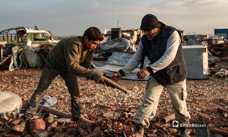 """يثق """"أبو أحمد"""" بعمله على تأمين القذائف غير المتفجرة لذا يسمح لأطفاله بالعمل معه في ساحة التجميع في ريف إدلب الشمالي - 5 آذار 2021 (عنب بلدي/ يوسف غريبي)"""