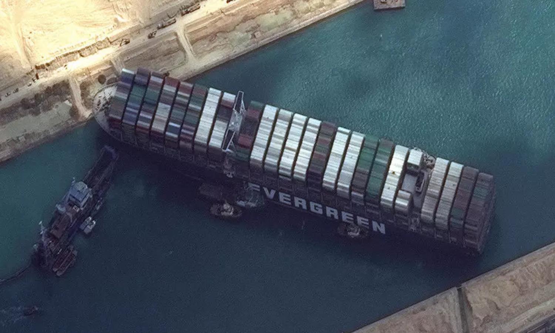 تظهر هذه الصورة الفضائية مرحلة من عملية إنقاذ سفينة الشحن إيفر جيفن التي كانت تغلق مجرى قناة السويس منذ 23 من آذار 2021 (AFP)