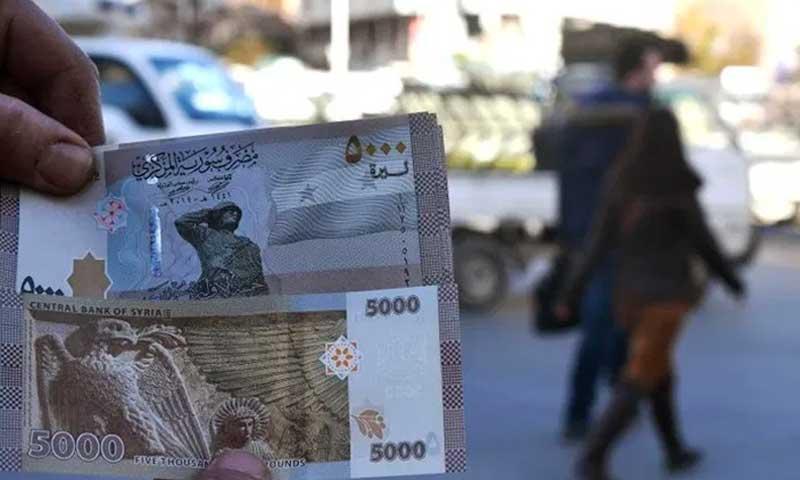 مواطن سوري يعرض عملة ورقية جديدة بقيمة 5000 ليرة سورية في دمشق - في 24 كانون الثاني 2021 (Ammar Safarjalani/Xinhua)