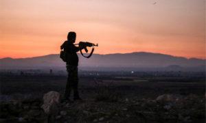 مقاتل من قوات المعارضة يوجه بندقيته نحو خطوط التماس في درعا - 2018 (AFP)