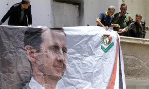 عناصر من الدفاع الوطني في سوريا يعلقون صورة رئيس النظام بشار الأسد على أحد المباني - 2015 (AFP)