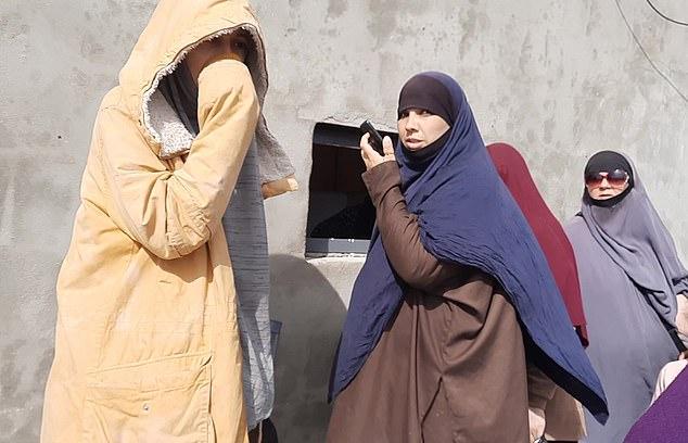 """مجموعة من النساء تتجمع حول """"البنك"""" في المخيم. تدفع البنوك الأموال التي ترسلها الأسرة والداعمون للأشخاص الذين يعيشون في المخيم 4 من نيسان (Mail online)"""