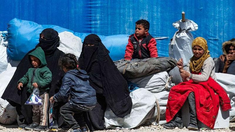 نساء وأطفال سوريون يجلسون في انتظار مغادرة مخيم الهول الذي يضم أقارب لمقاتلي الدولة الإسلامية. (AFP)
