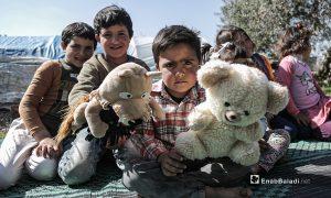 أطفال نازحين يشاهدون عرضا للدمى المتحركة قدمته فرقة الحارة المسرحية في إحدى مخيمات النازحين قرب مدينة إدلب 28 آذار 2021 (عنب بلدي/ تصوير يوسف غريبي).