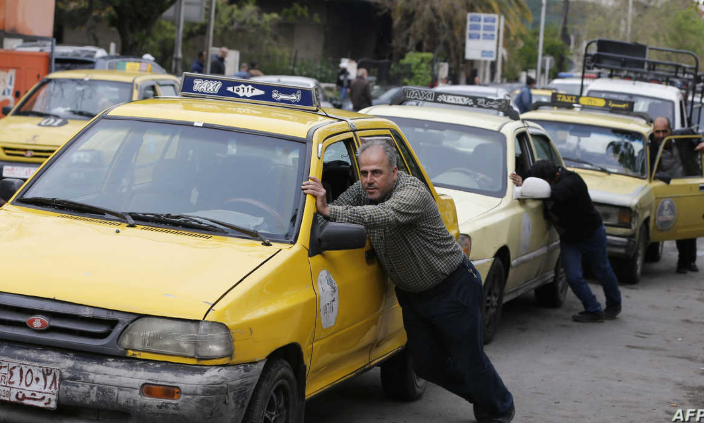 مواطنون يدفعون سياراتهم بسبب أزمة الوقود في دمشق (AFP)