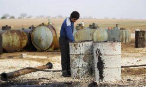 شاب يعمل في منشأة نفط بدائية في بلدة مارمارين في إدلب – 21 تشرين الثاني 2018 (رويترز)