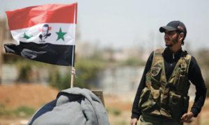 مقاتل مع الجيش السوري يقف بجانب علم بحمل صورة رئيس النظام بشار الأسد في درعا - تموز 2018 (رويترز)