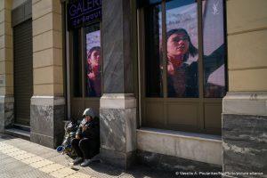 امرأة بلا مأوى في يوم عيد الميلاد أمام متجر لمستحضرات التجميل في وسط أثينا في 25 من كانون الأول 2020 ، أثينا ، اليونان (فاسيليس)