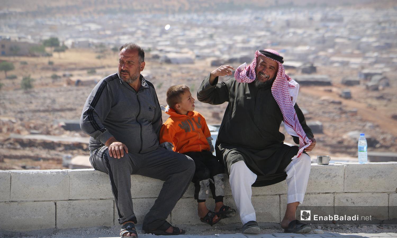 رجلان وطفل من قرية أم باطنة في مخيم أفاد في منطقة ديرحسان شمالي إدلب - 22 أيار 2021 (عنب بلدي - إياد عبد الجواد)