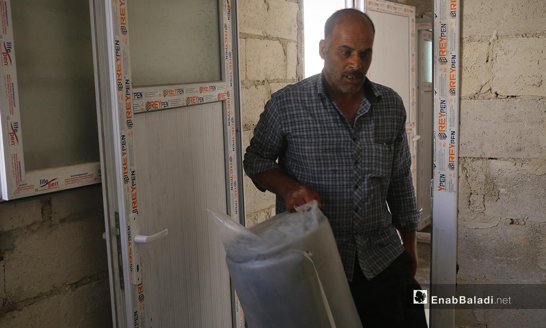 رجل من قرية أم باطنة يدخل أمتعته إلى داخل غرفته في مخيم أفاد في منطقة ديرحسان شمالي إدلب - 22 أيار 2021 (عنب بلدي - إياد عبد الجواد)