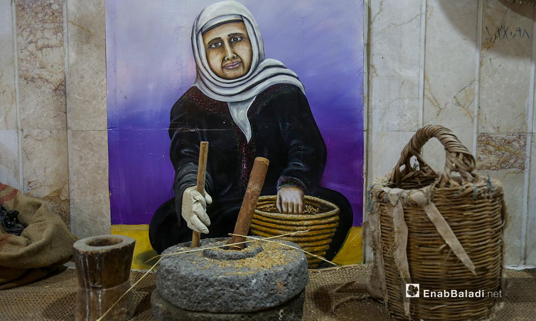 لوحة لسيدة ترتدي اللباس التقليدي وتقوم بطحن القمح بواسطة حجر قديم شباط 2021 (عنب بلدي - يوسف غريبي)