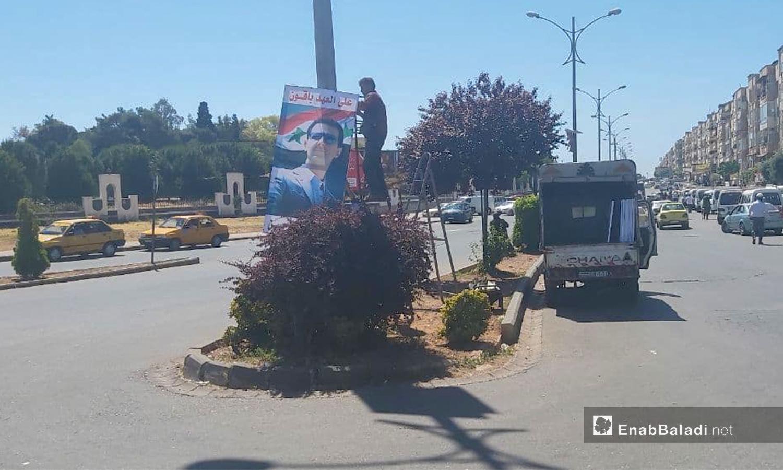لافتة تحمل صورة رئيس النظام السوري بشار الأسد تدعو المواطنين لإعادة انتخابه - 12 أيار 2021 (عنب بلدي/ عروة المنذر)