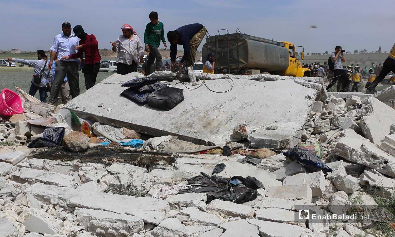 متطوعو الدفاع المدني وأهالي المنطقة يتفقدون مكان حدوث الانفجار-3 أيار 2021 (أنس الخولي/ عنب بلدي)