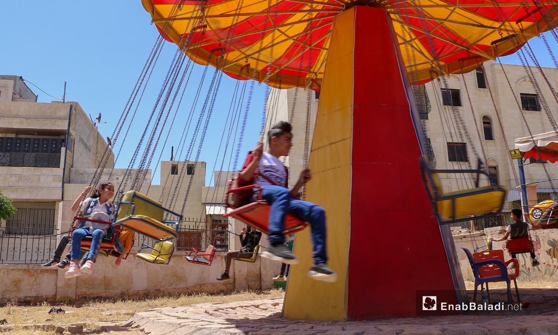 طفلان يركبان سيارة كهربائية في حديقة الألعاب أول أيام عيد الفطر- مدينة اعزاز بريف حلب، 13 من أيار 2021 (عنب بلدي/ وليد عثمان)