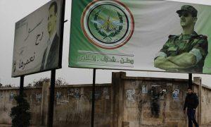 رجل يمشي وفوقه لافتة كتب عليها وطن شرف إخلاص تحمل صورة رئيس النظام السوري بشار الأسد في حلب - كانون الأول 2016 (AP)