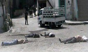 مقاتلون من قوات النظام يقفون قرب الجثث المرمية على الأرض في بلدة البيضا في بانياس بعد ارتكابهم مجزرة بحق سكانها - 2 أيار 2013 (AP)