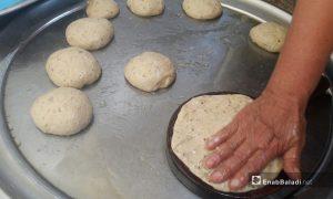 """امرأة تفرد عجينة حلوى """"خبز القالب"""" على القالب الخشبي المخصص لها في درعا - 12 أيار 2021 (عنب بلدي/ حليم محمد)"""