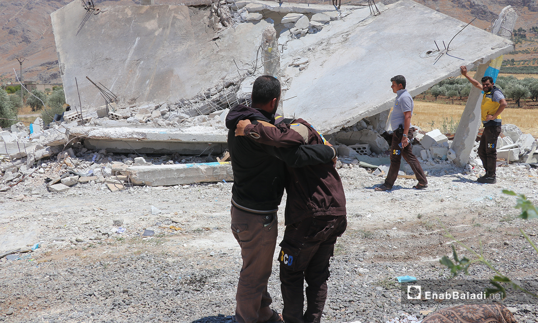 """عناصر من  """"الدفاع المدني السوري"""" يبكون زميلًا لهم، قُتل اليوم  باستهداف قوات النظام لمركز تابع للمنظمة، في قرية قسطون بسهل الغاب شمالي حماة، بشكل مباشر - 19 حزيران 2021(عنب بلدي/أنس الخولي)"""
