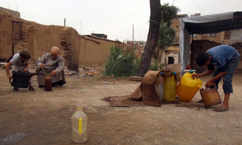 عائلة سورية تبيع المحروقات في القامشلي في 2015 (AFP)