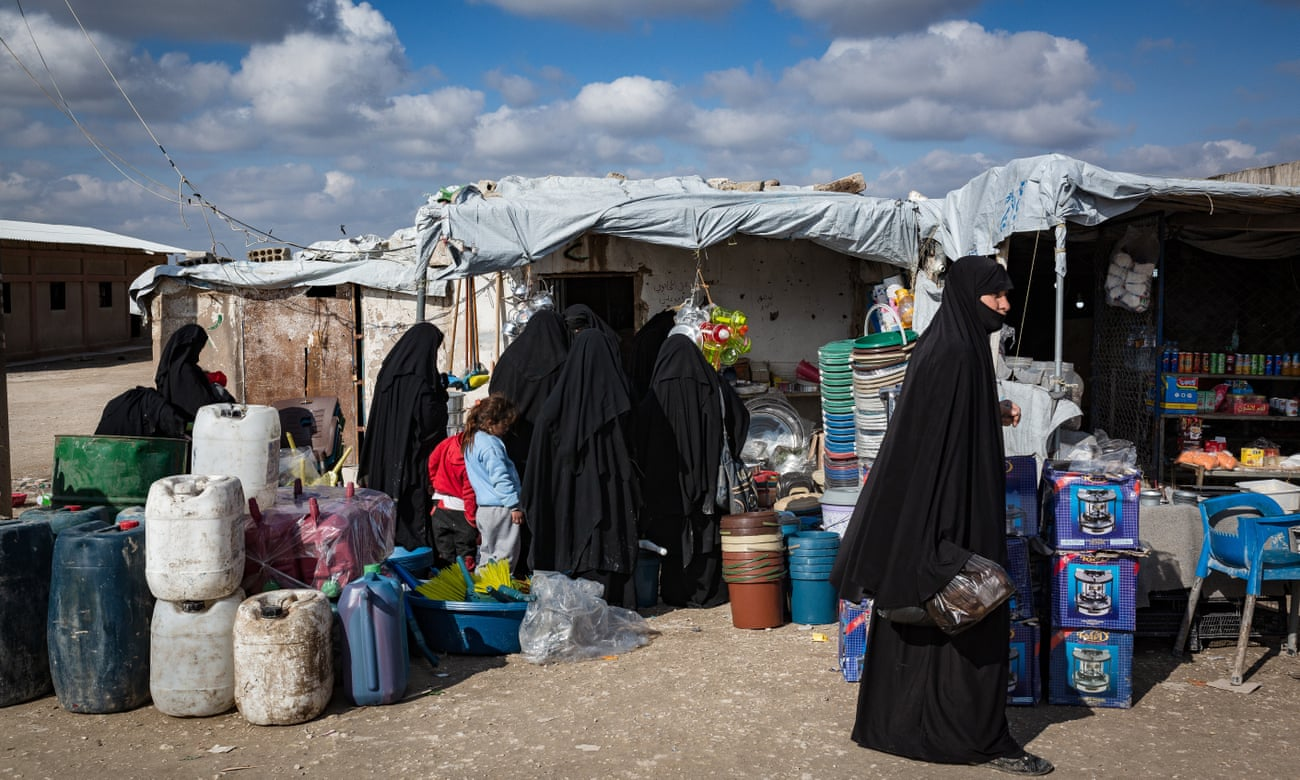 """نساء من عائلات التنظيم يتسوقن داخل سوق مؤقت في مخيم """"الهول"""" 2 من تموز. (The Guardian)"""