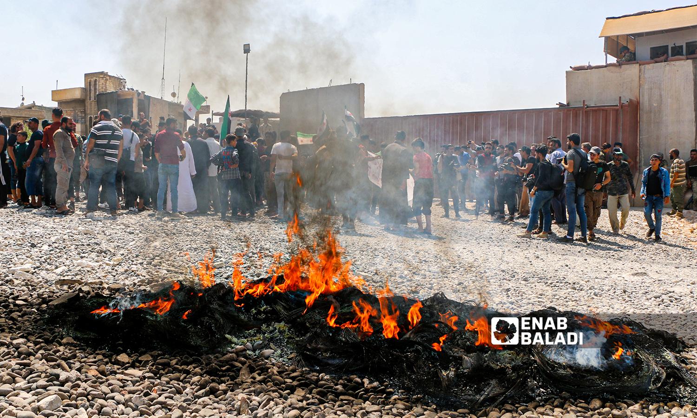 متظاهرون يحملون المسؤولية لضامن التركي مما يجري في إدلب أمام النقطة التركية في بلدة معترم جنوب إدلب - 23 تموز 2021 (عنب بلدي \ أنس الخولي)
