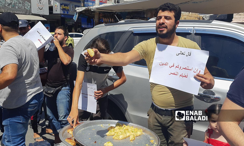 شبان في إدلب يرفعون لافتات تضامنية مع أهالي درعا ويوزعون الحلويات بمناسبة سقوط حواجز عسكرية للنظام السوري - 29 تموز 2021 (عنب بلدي/ أنس الخولي)