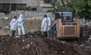عمال أثناء عمليات حفر عثرت على جثث مجهولة الهوية في عفرين شمال غربي سوريا (الأناضول)