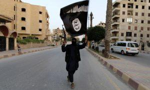 مقاتل من تنظيم الدولة الإسلامية يرفع راية التنظيم في شوارع مدينة دير الزور - (رويترز)