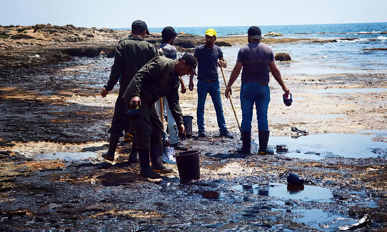 عمال ينظفون شاطئ بانياس من التسرب النفطي بأدوات بدائية (سانا)