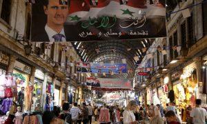 أشخاص يتسوقون في سوق الحميدية في مدينة دمشق قبيل الانتخابات الرئاسية (رويترز)