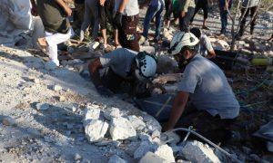 """عنصران من فريق """"الدفاع المدني"""" تنتشل ضحايا قصف للنظام على قرية بلشون بجبل الزاوية- 19 آب 2021 (الدفاع المدني السوري)"""