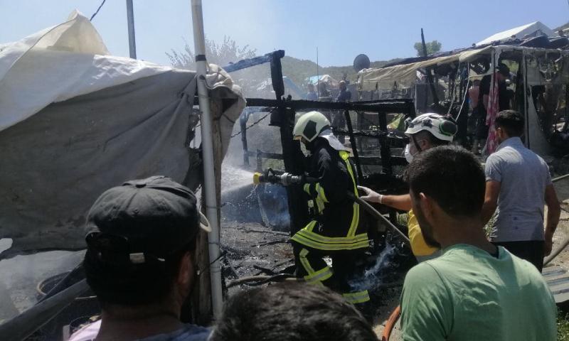 """عناصر إطفاء خلال عملية إخماد حريق نشب في في مخيم """"الجبل"""" بخربة الجوز غربي غرلب- 22 آب 2021 (الدفاع المدني السوري)"""