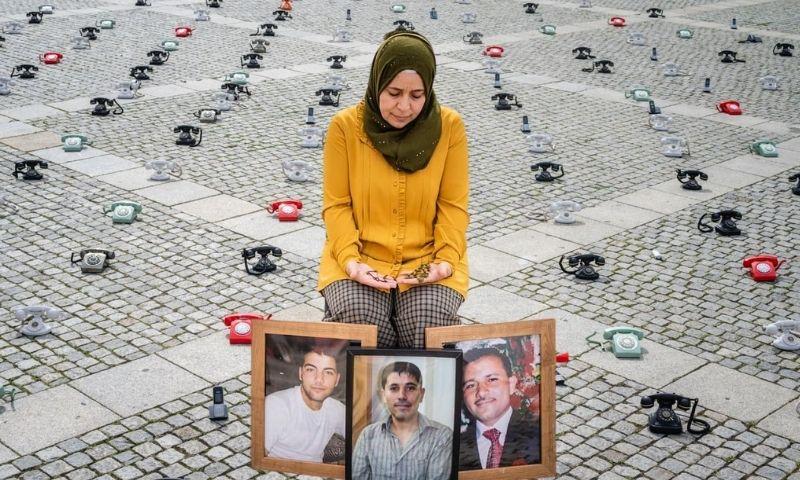 الناشطة السورية آمنة خولاني تجلس أمام صور أخوتها الثلاثة المعتقلين خلال وقفة تضامنية في برلين - 28 آب 2021 (تعديل عنب بلدي)