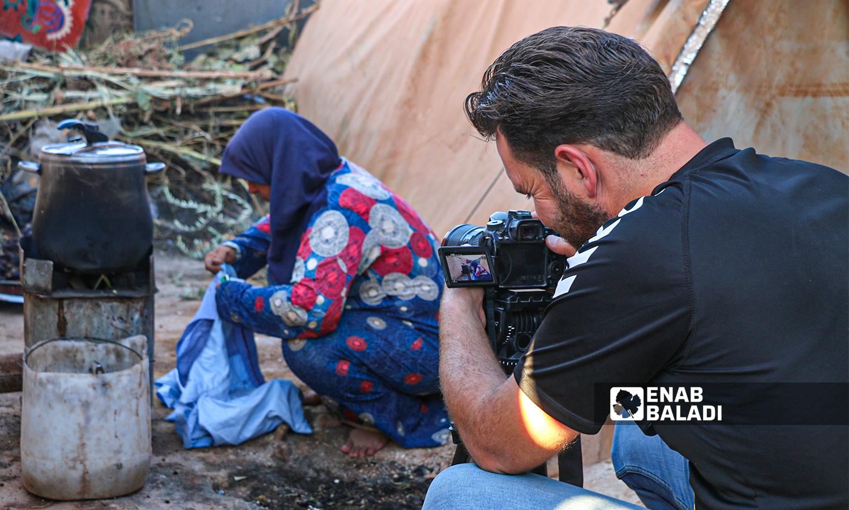 اعلامي يقوم بتصوير أمرأة مهجرة إفي مخيم السكة في بلدة حربنوش - 18 أيلول 2021 (عنب بلدي - إياد عبد الجواد)