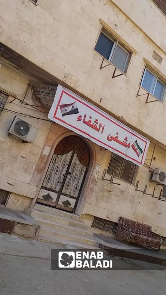 العلم الإيراني على لافتة مشفى الشفاء في دير الزور