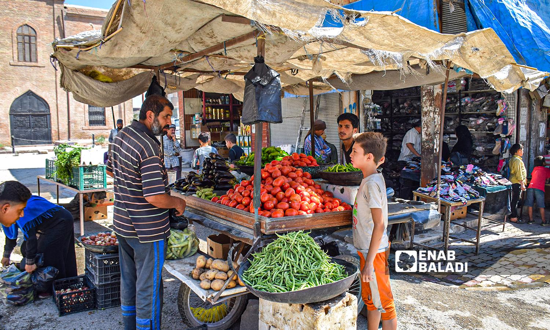 بسطة خضار يقف عليه طفل ومتسوقين 23 آب 2021 (عنب بلدي / حسام العمر)