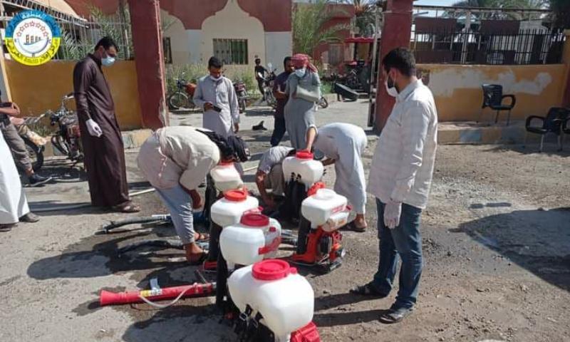 عمال يجهزون مرشات التعقيم أمام مبنى إحدى بلديات ريف دير الزور الشرقي- 22 أيلول2021 (مركز إعلام المنطقة الشرقية)