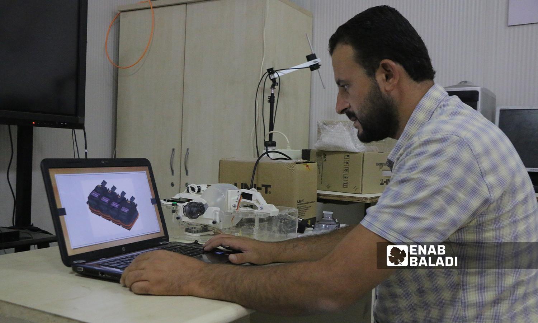 """الطالب زكريا الخلف اثناء تصميم جهاز التنفس الصناعي الذي ابتكره كمشروع تخرج لجامعة """"الشام"""" بريف حلب  5 تشرين الأول 2021 (عنب بلدي - وليد عثمان)"""