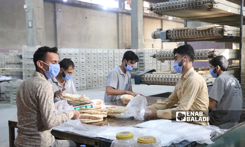 عمال يجهزون الخبز في الخط الأول للمخبز الآلي في مدينة الباب 8 تشرين الأول 2021 (عنب بلدي - سراج محمد)