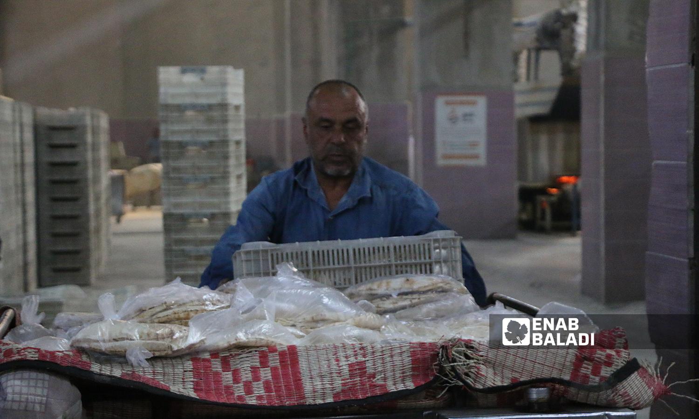 عامل يضع الخبز داخل الشاحنة تجهيزًا لنقله من المخبز الآلي في مدينة الباب 8 تشرين الأول 2021 (عنب بلدي - سراج محمد)