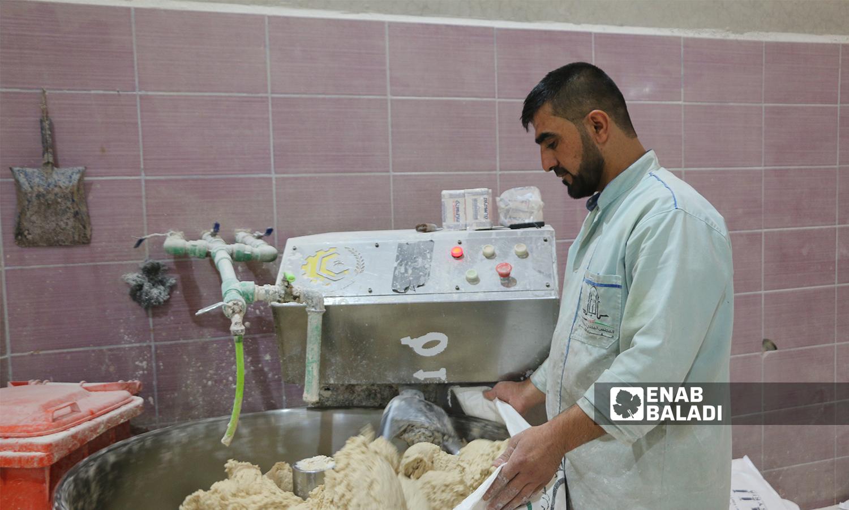 عامل يجهز العجين في المخبز الآلي يمدينة الباب 8 تشرين الأول 2021 (عنب بلدي - سراج محمد)