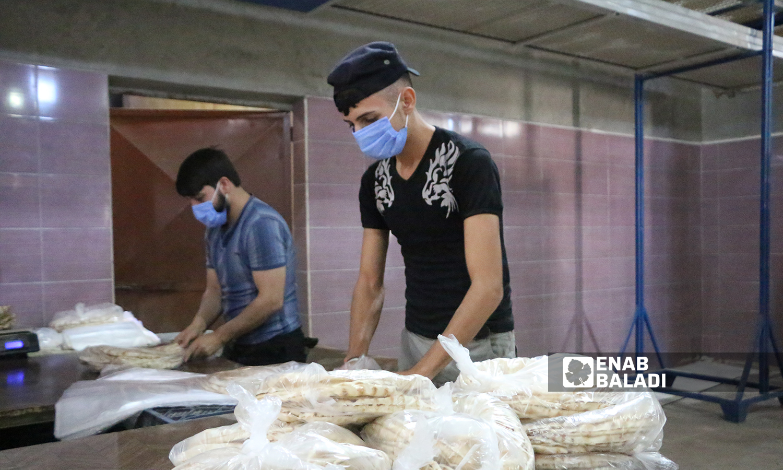 عمال يعبئون الخبز في أكياس النايلون داخل المخبز الآلي لمدينة الباب  8 تشرين الأول 2021 (عنب بلدي - سراج محمد)