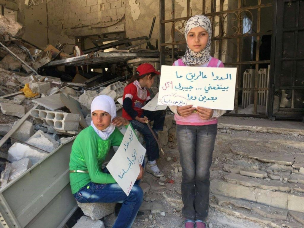 """""""Medication to empty stomach does not do me good… bring me food, so I can have medication"""". Children waiting for the promised aid convoy. Image source: Local Council of Daraya City."""