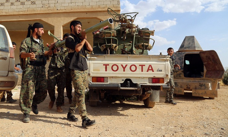 """Elements of """"Democratic Syria"""" forces on/over the land skirts of the city of Manbij – Thursday, June 23rd (AFP)"""