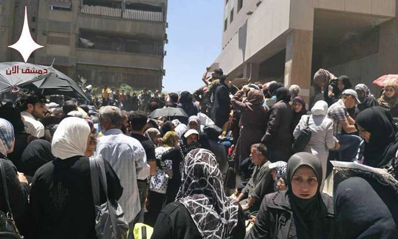 (Crowds of hundred people gathering in front of a Charity building in Al-Maydan neighborhood in the city of Damascus – June, 10th, 2016 – Damascus Now)